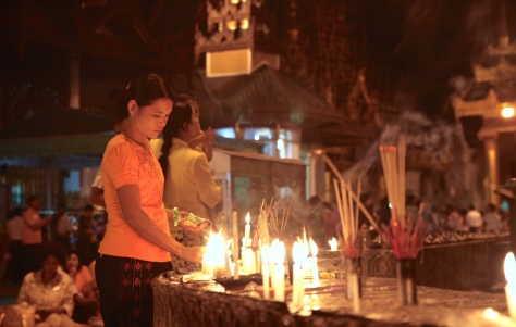 woman lighting incense at the shwedadon pagoda